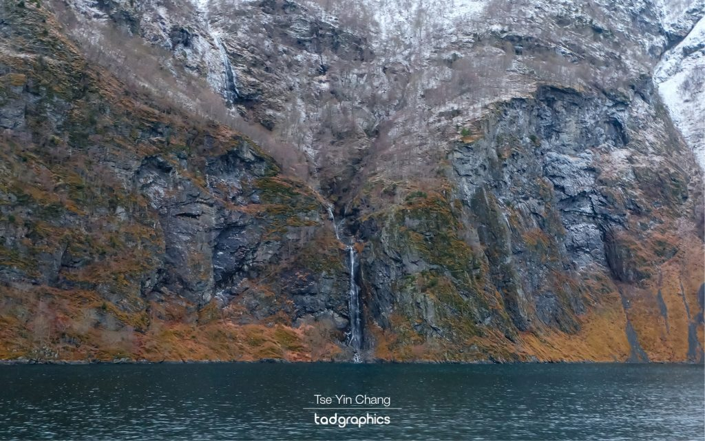 The sides of the fjord were punctuated by mighty waterfalls clinging on to the cliffs at impossible angles